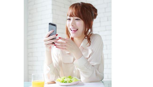 女性がスマホをしながら食事
